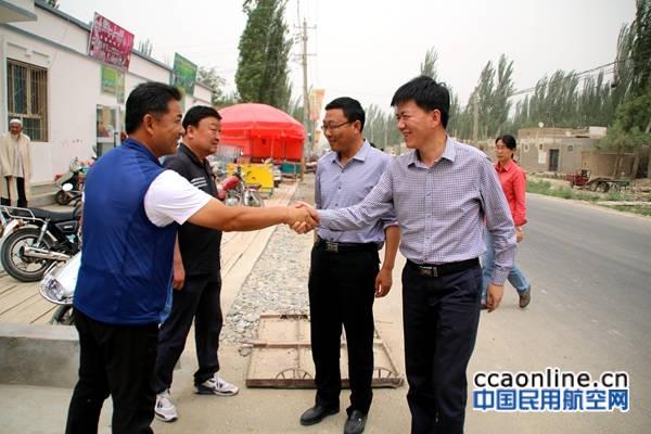 图为新疆机场集团住于田县巴什喀群村工作组组长陶润文在村委会门口欢迎观摩团带队领导